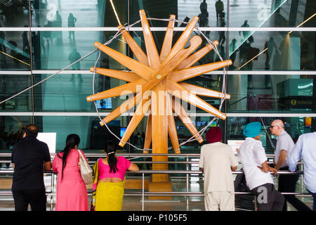 NEW DELHI, INDIA - CIRCA APRIL 2017: People stand in front of the world's largest charkha (spinning wheel) at Indira Gandhi International Airport. - Stock Photo