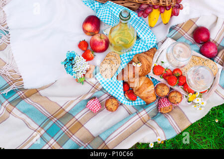 picnic basket and food. A bottle of wine and two glasses. Romanica. Green meadow with flowers. Spring in the Netherlands. Holidays. View from above. - Stock Photo