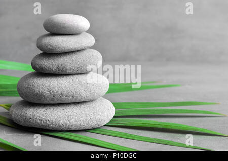 Stones balance and green palm leaf. Zen and spa concept. - Stock Photo
