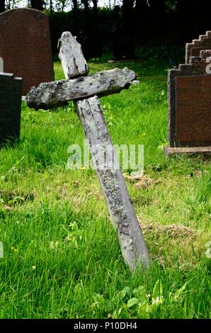 Lichen growing on a simple wooden cross grave marker in the graveyard of St Decumans Church Rhoscrowther  Pembrokeshire Wales Cymru UK - Stock Photo