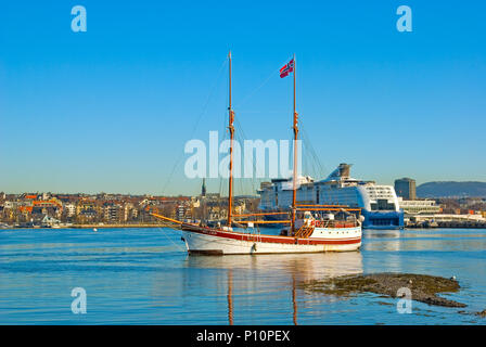 OSLO, NORWAY - APRIL 12, 2010: Bygdoy Peninsula. Sailing ship with norwegian flag against the background of the coast of Oslo and cruise liner - Stock Photo