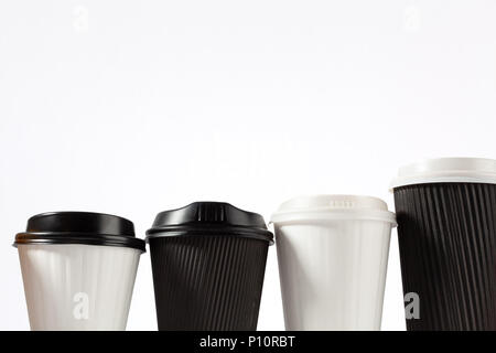 Four plastic coffee cups in a row on white background with copy space - Stock Photo