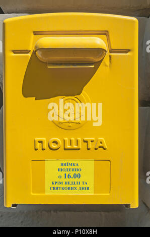 A classical yellow postbox on Ukrainian post office hanging on the wall - Stock Photo