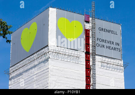 Grenfell Tower where at least 72 people died after a fire broke out on June 14th 2017 in North Kensington with the slogan 'Forever in our Hearts'. - Stock Photo