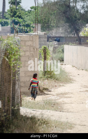 Saint-Louis, Senegal - October 20, 2013: Unidentified young African boy with colorful shirt walking through sandy street - Stock Photo