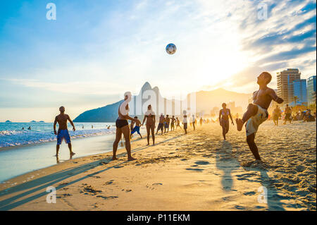 RIO DE JANEIRO - APRIL 01, 2014: Groups of young Brazilians play keepy uppy, or altinho, at sunset on the shore of Ipanema Beach at Posto 9 - Stock Photo