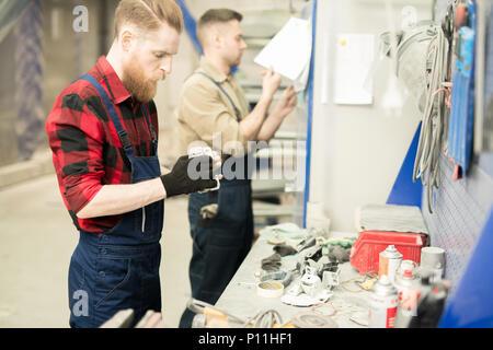 Mechanics Working In Repair Shop - Stock Photo