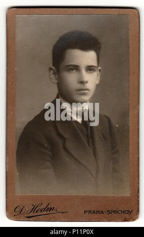 PRAGUE, THE CZECHOSLOVAK REPUBLIC - CIRCA 1920s: Vintage cabinet card shows young boy wears posh garment. Antique black white photo with sepia tint. - Stock Photo