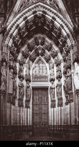 The North portal of the West facade at Cologne Cathedral is also called 'Portal of the Three Kings' or 'Magi portal'. The tympanum above the door shows in the lower section the Three Kings before Herod and in the upper part The Adoration of the Magi. - Stock Photo
