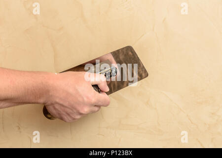 Man's hand put a Venetian cloth on the wall 2018 - Stock Photo