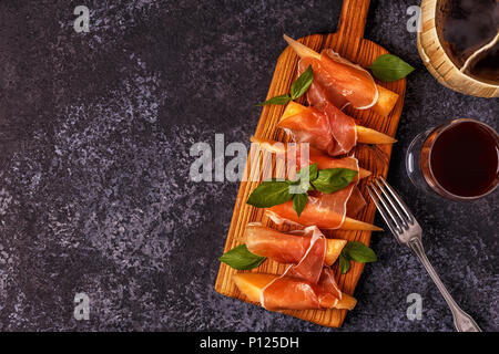 Fresh melon with prosciutto and basil. Top view  with copy space. - Stock Photo