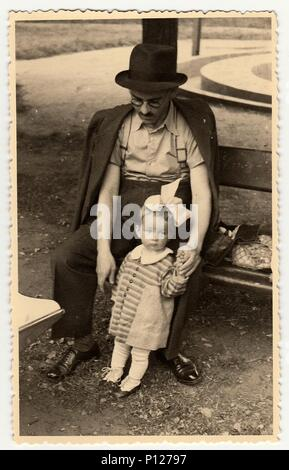 HODONIN, THE CZECHOSLOVAK REPUBLIC - CIRCA 1942: A vintage photo shows small toddler girl and  father. Toddler shows sad face. - Stock Photo