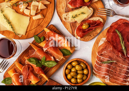 Italian food  background with ham, cheese, olives, bread, wine. - Stock Photo