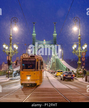 A passing tram driver gives a thumbs up on a snow covered Liberty Bridge in Budapest - Stock Photo