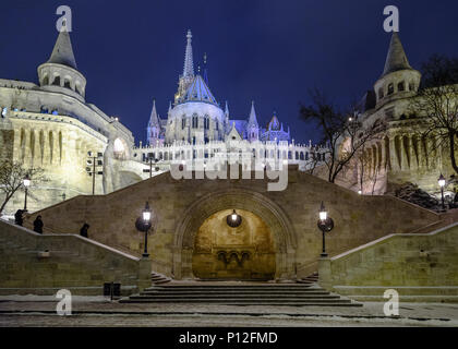 Looking up at a snow covered Fisherman's Bastion and Matthias Church in Budapest in winter - Stock Photo