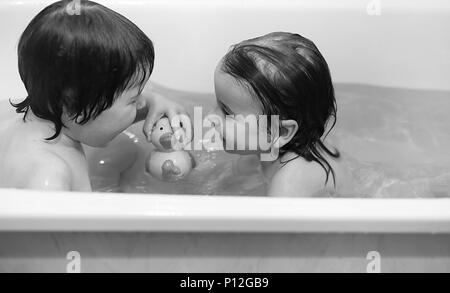 Young children take a bath. Children wash in bathroom. Brother and sister play in the bathroom during water procedures. - Stock Photo