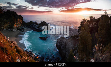 Sunset with beach, cove, forest and waterfall. McWay falls, Big Sur, California - Stock Photo