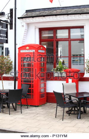 Red Post Box & Red Telephone Box Outside Giovanni's Italian Restaurant On King Street, Knutsford, Cheshire England. Summer June 2018 - Stock Photo