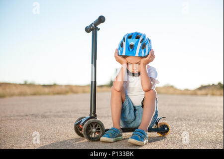 sad tired little boy in sport helmet sitting on scooter on road head down - Stock Photo