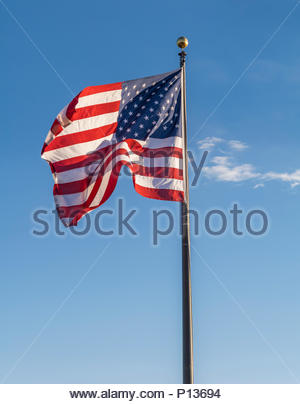 American flag waving in wind against a blue sky - Stock Photo