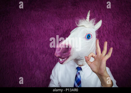 Freaky young man in comical mask stands on purple background. Portrait of unusual manager. Funny unicorn in shirt and tie is showing gesture alright - Stock Photo
