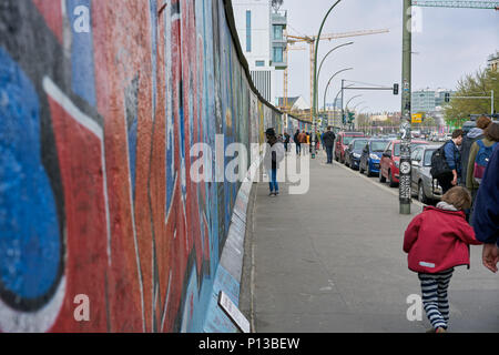 Berlin, Germany - April 5, 2017: Tourists seeing the paints at the Eastside gallery in Berlin - Stock Photo
