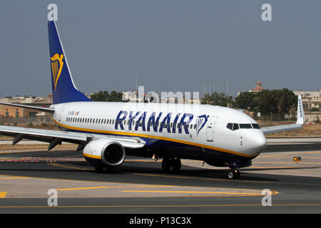Boeing 737-800 commercial passenger jet belonging to low cost airline Ryanair taxiing on taxiway at Malta Airport. Mass tourism and cheap air travel. - Stock Photo