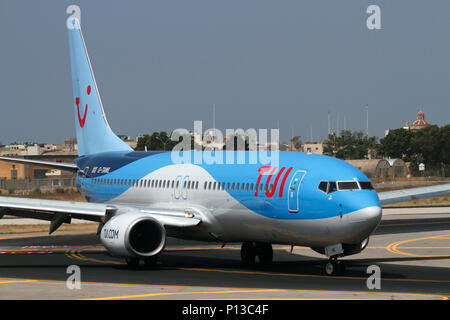 TUI Airways Boeing 737-800 passenger jet plane taxiing on arrival in Malta. Air travel and tourism. - Stock Photo