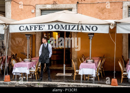 Italian waiter stands outside Caffe Domiziano on Piazza Navona waiting for customers on a rainy day, empty tables, outdoor dining, restaurant name. - Stock Photo