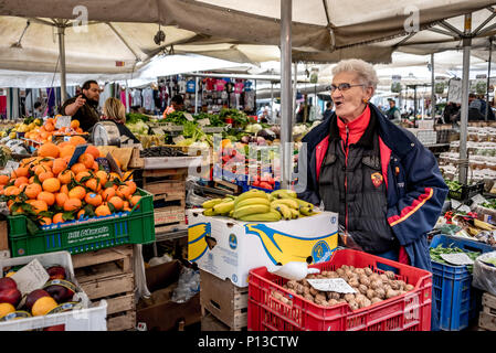 Old Roman woman selling produce at Campo De Fiori open air market in Rome, Italy, with colorful tangerines, bananas, and walnuts, colorful vegetables - Stock Photo