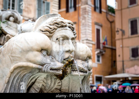 Face of a triton with two dolphins in Fontana del Moro / Moor Fountain at Piazza Navona, Rome, Italy, with colorful tourist umbrellas and orange walls - Stock Photo