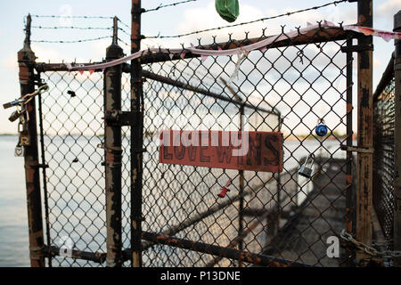 A handwritten Love Wins sign on a chain link fence along the Mississippi River in New Orleans, Louisiana. - Stock Photo