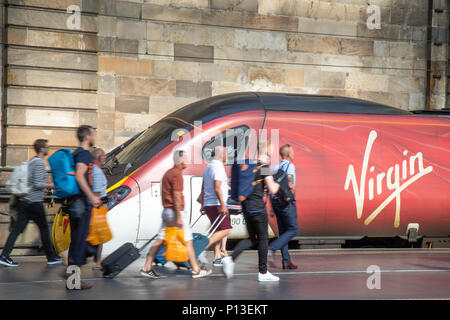Passengers boarding a Class 390 Virgin Pendolino tilting train at platform one of Glasgow Central - Stock Photo