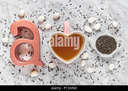 Tea in a heart-shaped mug, white chocolate, green tea leaves and metal letter A. Flat lay composition on marble background. - Stock Photo