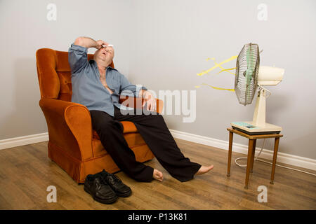 A man sitting in front of an old fashioned fan sweating and wiping brow. - Stock Photo