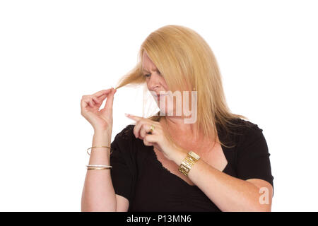 A mature woman looking at her hair and noticing the split ends. - Stock Photo