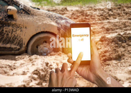 Man hand using smartphone calling emergency for help car tire stuck in the mud background. Car wheel in the mud clay can not run out. - Stock Photo