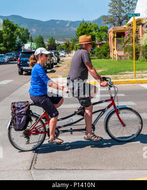 Middle-aged couple riding a tandem bicycle in the small mountain town of Salida; Colorado; USA - Stock Photo
