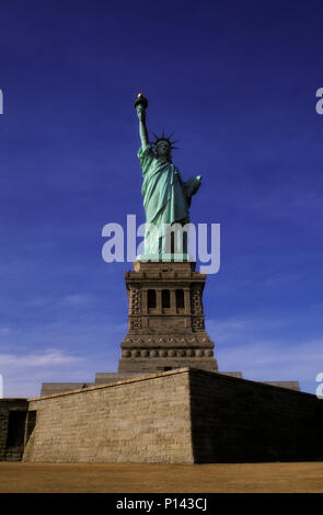Statue of Liberty, frontal view on axis on Liberty Island with late light and deep shadow, New York, NY, USA - Stock Photo