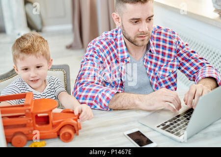 Young Father Working from Home - Stock Photo