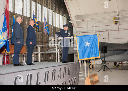 United States Air Force Maj. Gen. H. Michael Edwards, the Adjutant General of Colorado and U.S. Air Force Col. Floyd Dunstan, Assistant Adjutant General - Air, Colorado National Guard, stand at attention as U.S. Air Force Master Sgt. Wolfram Stumpf unfurls the general officer flag for presentation to Dunstan during his promotion to Brigadier General, May 6, 2017, at Buckley Air Force Base, Aurora, Colo. Upon promotion to the general officer ranks, also known as flag officers, it is customary to be presented with a personal flag, representing their command authority. - Stock Photo