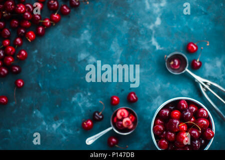 Fresh cherries on a concrete background with a small metal bucket and an ice cream spoon. Making summer dessert concept flat lay with copy space. - Stock Photo