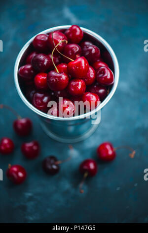 Cherries with a small metal bucket on a grey concrete background, summer berries concept with copy space. Neutral color tones still life - Stock Photo