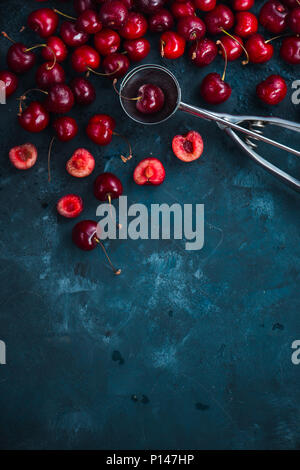 Cherries and ice cream spoon on a grey concrete background, summer berries concept with copy space. Making dessert flat lay in neutral color tones - Stock Photo