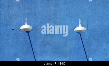 Blue stucco wall with light fixtures and shadows in daytime - Stock Photo