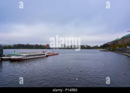Hamburg, Germany - April 7, 2017: View of the Alster fountain in Hamburg with a tourist boat on the background - Stock Photo