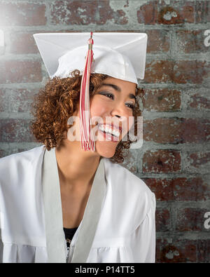 Beautiful Natural smiling mixed race girl in white cap and gown with red and white tassels against a brick wall background - Stock Photo