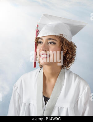Gorgeous mixed race young lady with curly brown hair in a white cap and gown with red and white tassel - Stock Photo