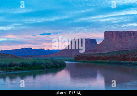 A majestic pink sunset along the Colorado River with a view over two butte rock formations located between Moab and the Arches National Park, Utah, US - Stock Photo