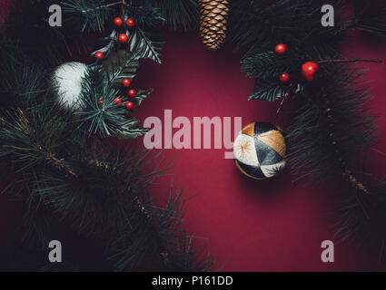 Christmas ball and fir branches for wreath with cherry and pine cone on red table background. winter holiday festive celebration concept - Stock Photo